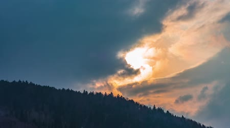 Timelapse of clouds passing over mountain at sunset