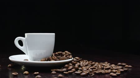 çuval bezi : A cup of hot coffee with roasted beans around on a black background in 4k resolution in slow motion Stok Video