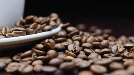 drinking coffee : A cup of hot coffee with roasted beans around on a black background in 4k resolution in slow motion Stock Footage