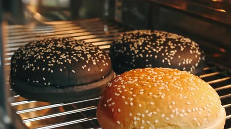 gergelim : Hot burger rolls with seeds are baked in the oven in 4k resolution in slow motion Vídeos