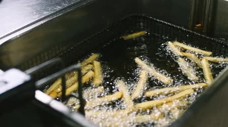 Proces om frieten in de friteuse in 4k-resolutie in slow motion te koken