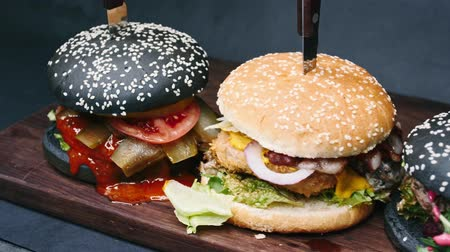pepř : Three charcoal burgers are on the board, pierced with a knife, and ready to eat in 4k resolution in slow motion chamber passage