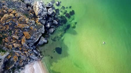 krym : Aerial View: Flight over the сoast. GIrl is swimming in the sea on General beach, near Kerch, Crimea in slow motion