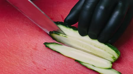 picada : Cutting a cucumber with a knife on a red cutting board in black gloves in 4k resolution Vídeos