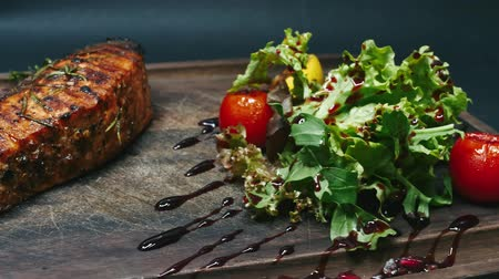 soy : Steak with sauce, tomatoes and greens on a wooden board. Driving on a slider in 4k resolution
