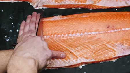 Chef takes out bones from the salmon fillet, cutting fish on slices for cooking sushi in 4k resolution in slow motion 動画素材