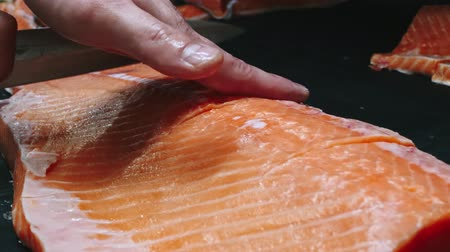 meat rolls : Chef takes out bones from the salmon fillet, cutting fish on slices for cooking sushi in 4k resolution in slow motion Stock Footage