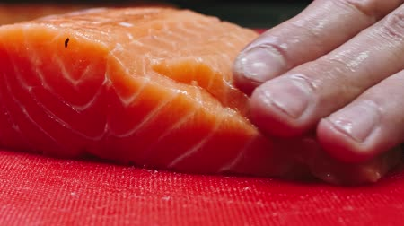 hentes : Chef takes out bones from the salmon fillet, cutting fish on slices for cooking sushi in 4k resolution in slow motion Stock mozgókép