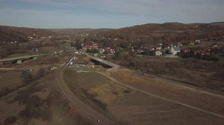 Birds-eye view of the traffic interchange under construction in a picturesque hilly area. Panorama of the intersection of the railway and highway. Flight drone over the bridges over the river Stock Footage
