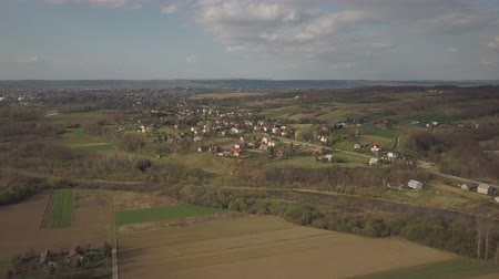 Panorama from a birds eye view. Central Europe: The Polish village is located among the green hills. Temperate climate. Flight drones or quadrocopter. Urbanization of the landscape