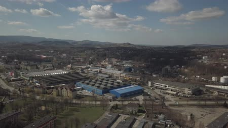 дымоход : Gorlice, Poland - 4 5 2019: Industrial region of the Carpathian city. Top view of the refinery and auxiliary buildings. Video shot by drone or quadrocopter. Vanity of the day at the factory.