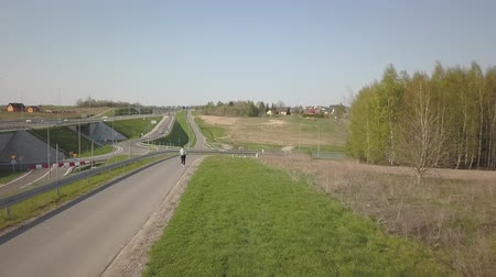 Young girl in sports uniform runs along the asphalt road along the highway. Healthy lifestyle and sports training. Panorama of the motorway with a birds eye view. The movement of vehicles on the highway. Landscape design of communication paths