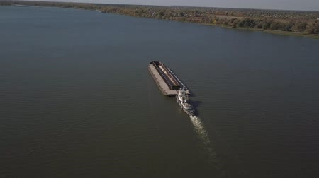 A tugboat ship pushes a barge upstream of the river to transport bulk materials. Aerial photography with a quadcopter or a drone. Panorama of the Dnieper - the main water transport artery of Ukraine Stock Footage
