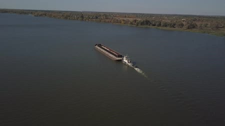 タンカー : A tugboat ship pushes a barge upstream of the river to transport bulk materials. Aerial photography with a quadcopter or a drone. Panorama of the Dnieper - the main water transport artery of Ukraine 動画素材