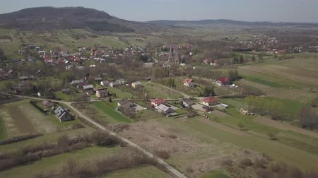 Cieklin, Poland - 7 7 2019: Roman Catholic Church in the center of a picturesque village located on green hills. Aerial drone or quadrocopter aerial view. European farms. Private Farm Panorama Stock Footage