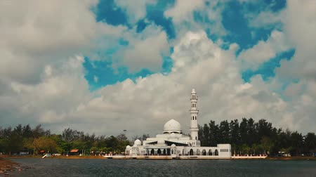 cami : Timelapse footage of Tengku Tengah Zaharah Mosque or Floating Mosque in Kuala Terengganu, Malaysia with perfect reflection with fast moving clouds under bright sunny day