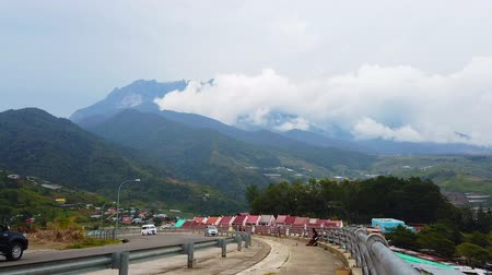 malajsie : SABAH, MALAYSIA - SEPTEMBER 2019: Panoramic view of Kundasang town with Mount Kinabalu background Dostupné videozáznamy