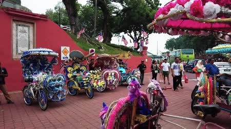 コロニアル : MALACCA, MALAYSIA - 15 SEPTEMBER 2019: Colorful rickshaws on the Dutch Square in Malacca City ready for tourist ride 動画素材