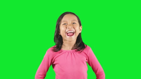vzrušený : Adorable little girl laughing and looks happy, standing in the studio with green background