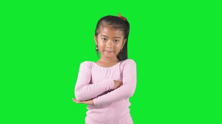 polegar : Little girl standing in the studio and looks confident while folded hands and showing thumb up with green background Vídeos