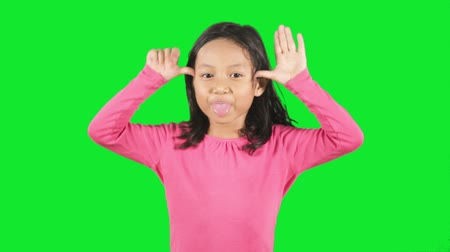 ostoba : Funny little girl showing a silly face expression in the studio with green background