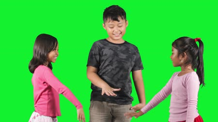 дружба : Three cheerful children playing hands together in the studio with green background