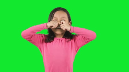 olhos verdes : Expressive little girl crying while standing in the studio with green background Stock Footage