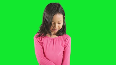 félénk : Cute little girl standing in the studio and looks shy, shot with green background
