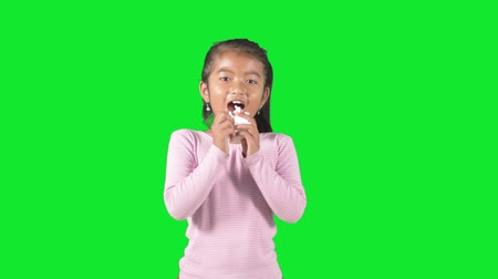 alergia : Sick little girl sneezing on a tissue while standing in the studio with green background
