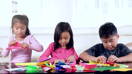 zabawka : Three creative children playing origami paper on the table at home