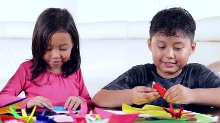 bird learning : Two happy children playing origami together on the table at home Stock Footage