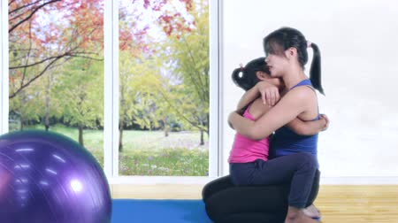 asian family : Young woman wearing sportswear and hugging her little daughter with fitness ball on the floor at home