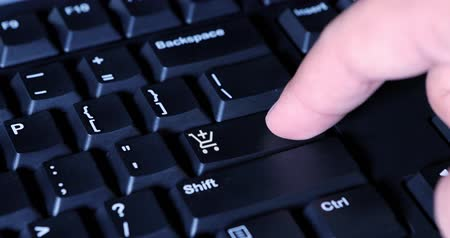 add to cart : Human finger presses a shopping cart button on the computer keyboard