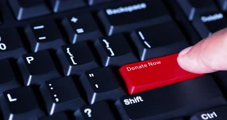 способствовать : Human hand pressing a red button with text of Donate Now on the computer keyboard Стоковые видеозаписи