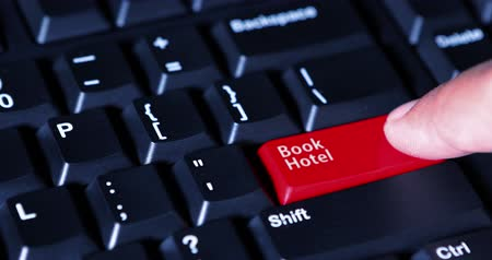 reklama : Close up of a male finger pressing a Book Hotel button with red color on the computer keyboard
