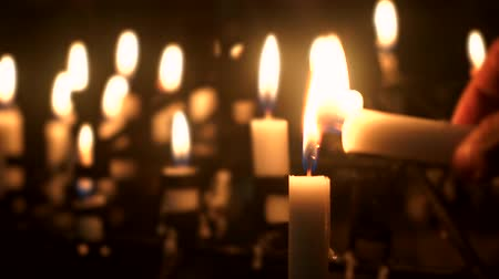 easter : Video footage of hand burns a candle in the church at night with a candle light