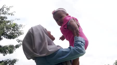 başörtüsü : Video footage of happy muslim mother wearing scarf and playing with her baby. Shot outdoors