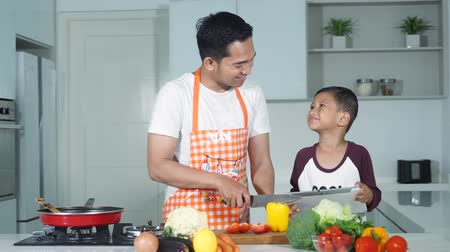 culinária : Little boy and his father cooking vegetables in the kitchen at home