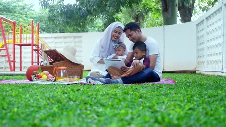 ислам : Video footage of happy muslim family taking selfie photo while enjoying picnic together at the park