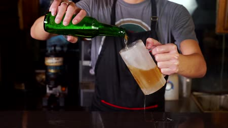 beer tap : Video footage of a male bartender wearing apron and pouring a bottle of cold beer into glass