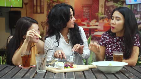 comida japonesa : Group of three cheerful women eating beef steak and french fries while chatting and having fun together in the cafe Vídeos
