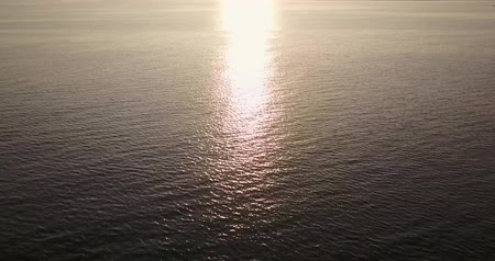 serene : Aerial view footage of beautiful landscape of the calm ocean with sunset reflection on the water Stock Footage