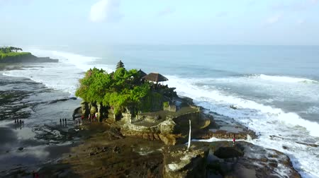 множество : Aerial footage of beautiful landscape above Tanah Lot Temple with tourists and frothy wave in Bali, Indonesia. Shot in 4k resolution