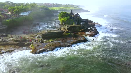 множество : Beautiful aerial landscape footage of Tanah Lot Temple with frothy wave from a drone flying around the temple in Bali, Indonesia. Shot in 4k resolution