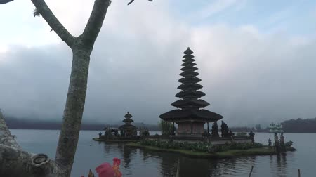 danu : Beautiful landscape footage of Ulun Danu Bratan Temple with cloudy sky and a tree as a frame in Tabanan, Bali, Indonesia.