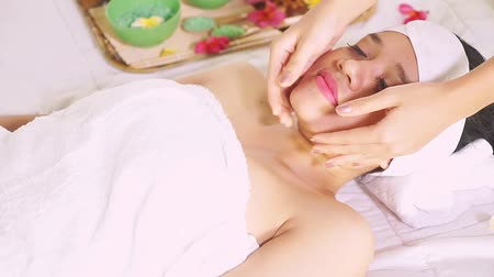 salt bed : Video footage of a beautiful young Asian woman enjoying face massage in the beauty salon while lying on the bed