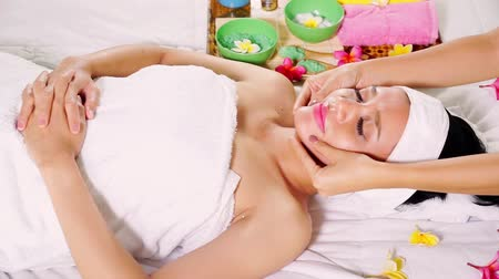 salt bed : Video footage of a young pretty woman getting face massage at beauty salon while lying on bed Stock Footage