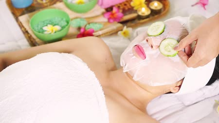salt bed : Video footage of a young woman getting facial treatment with mask, cucumber, and massage in the beauty salon Stock Footage