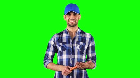 csavarkulcs : Male Caucasian plumber holding a wrench and smiling at the camera while standing against green screen background