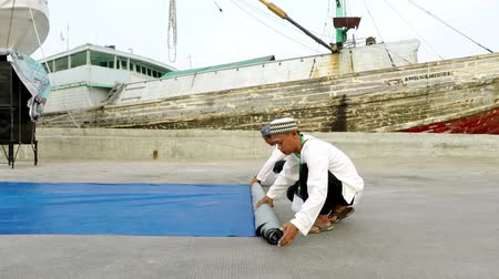 furl : JAKARTA, Indonesia. September 19, 2017: Two muslim men tidying tarpaulin after praying in Sunda Kelapa Old Harbor